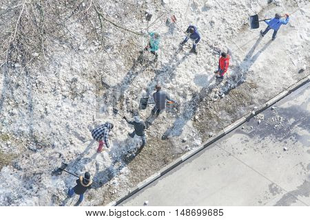 residents of high-rise building clean area of yard with snow, above view