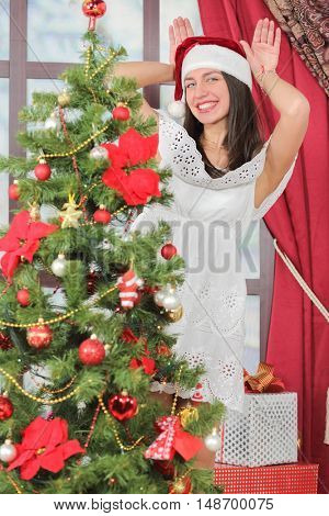 Portrait of woman near Christmas tree. Girl in white dress and Santa hat depicts rabbit
