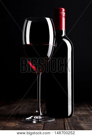 Red wine bottle and glass on wooden table black background