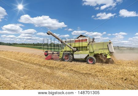 Working combine harvester during harvest on a grain field in sunlight