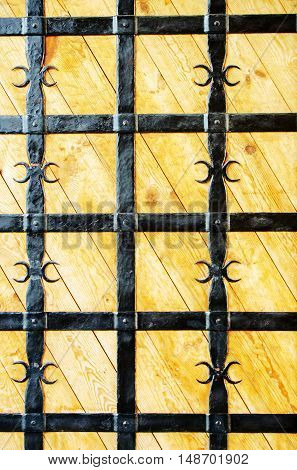Wooden doors with wrought-iron grate. Close-up. Outdoor.