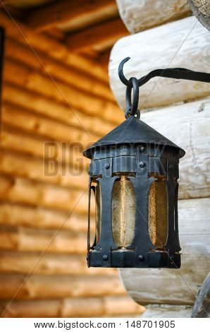 Black metal lantern on an iron hook. In the historical park