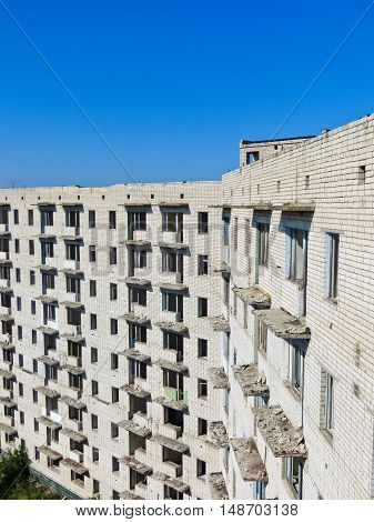 An abandoned multistory building in Ukraine against blue sky