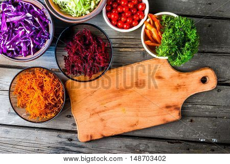 Selection of autumn vegetables, rich in vitamins. Set for cooking fresh salad or vegetable stew. In the glass, ceramic and clay bowls on a wooden table, top view. Next to the cutting board