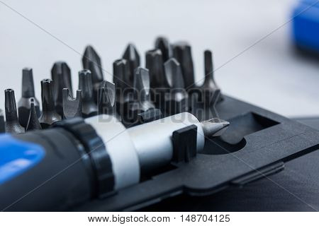 Tool set screwdriver with different nozzles and screws macro on gray concrete background