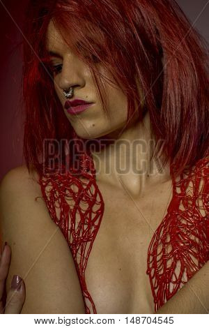 piercing, beautiful redhead with pierced nose and red corset lace frills wax