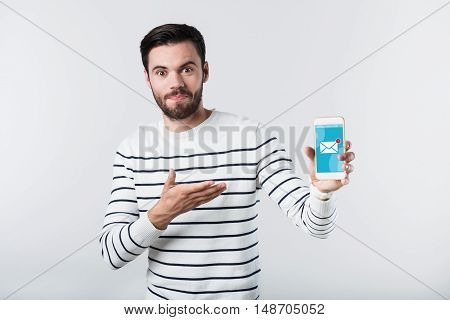 Amazing finding. Young handsome man astonishing and pointing on cellphone while standing against white background.