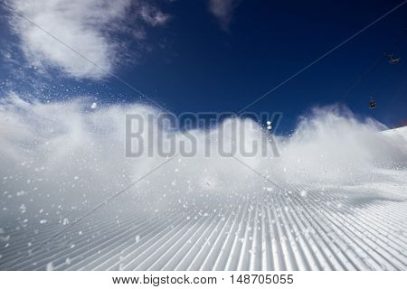 Snow dust cloud after skier or snowboarder on the ski slope. Sheregesh resort, Siberia, Russia.