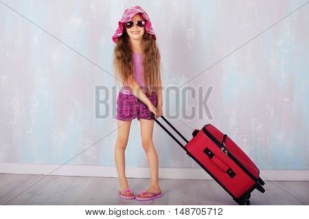 beautiful little girl carrying a suitcase. The concept of travel and lifestyle.