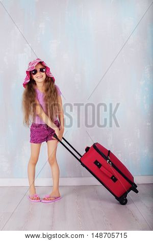 funny child with a suitcase goes on a journey