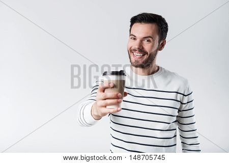 Be cheerful. Glad handsome bearded man smiling and showing coffee while standing against white background.