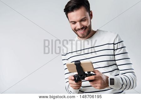 Such an interesting game. Young happy man smiling and using portable gamepad while standing against white background.