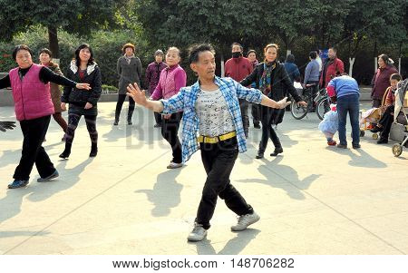 Pengzhou China - December 11 2013: A group of Chinese people doing Tai 'chi exercises in a public park