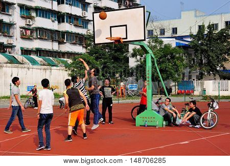 Pengzhou China November 8 2013: A group of Chinese youths playing basketball on a court at Pengzhou National Stadium