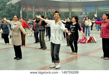 Pengzhou China - November 6 2009: A large group of Chinese dancing in unisom in the open plaza at New Square