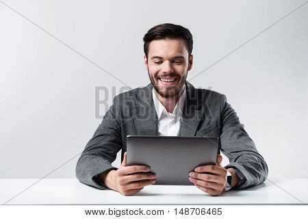 Work with pleasure. Young handsome man smiling and using tablet while standing against white background.