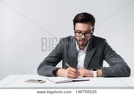 I am busy. Young handsome ambitious man sitting at the table and making notes while located against white background.