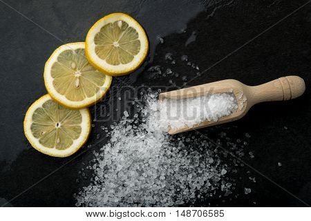 salt and lemon seen from above on a black stone