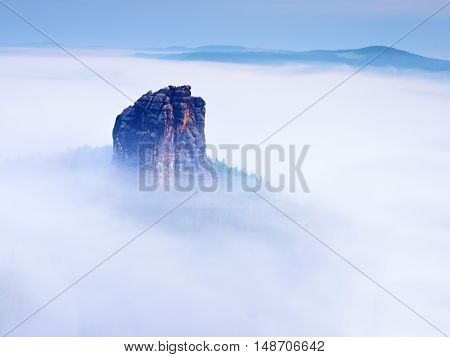 Sharp Sandstone Rock Empire Sticking Out From Heavy Fog. Deep Misty Valley