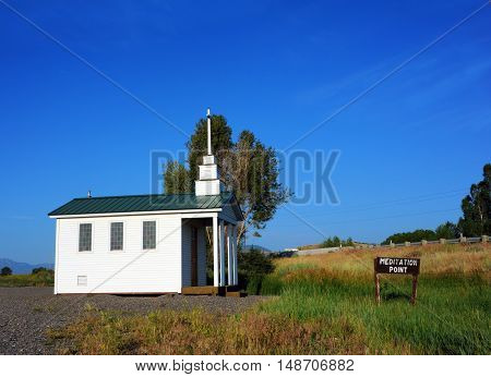 Tiny tiny church is place of refuge in Emigrant Montana. Church is white green roof and tiny steeple.