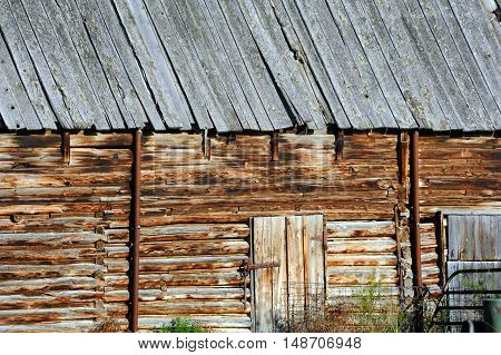Barn wall shows notched logs on old pole barn. Closeup of wall and entry.