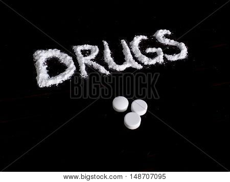 Cocaine drug powder in drugs word shaped and tablets on black background