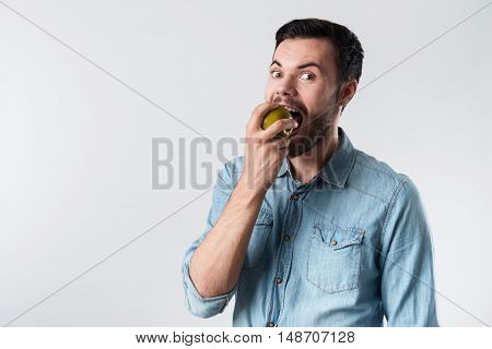 So tasty. Young handsome man staring and eating apple while standing against white background.