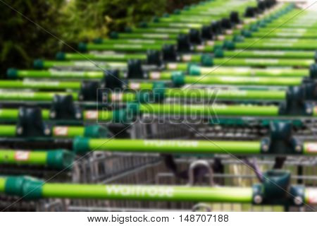 BEACONSFIELD ENGLAND - JUNE 2016: Waitrose shopping trollies outside store in Beaconsfield Out of focus.