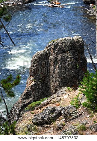 Closeup of huge rock that clings to the shoreline of the Firehole River in Yellowstone National Park.