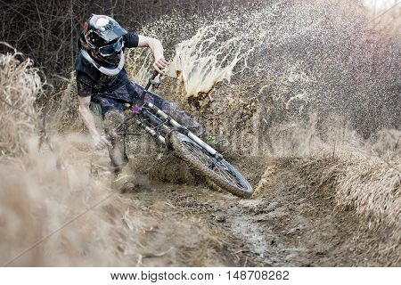 Mountainbiker rides on path in mud and water