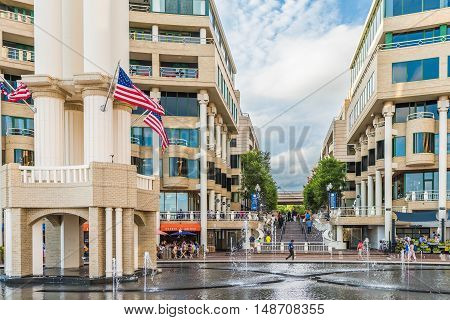 Washington DC, USA - August 5, 2016: Georgetown outdoor mall with restaurants and large fountain on Potomac riverfront with people walking