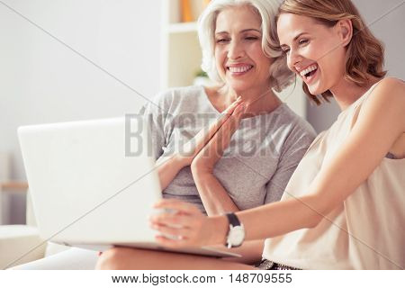 Express your feelings. Cheerful delighted woman and her aged mother sitting on the couch and smiling while using laptop
