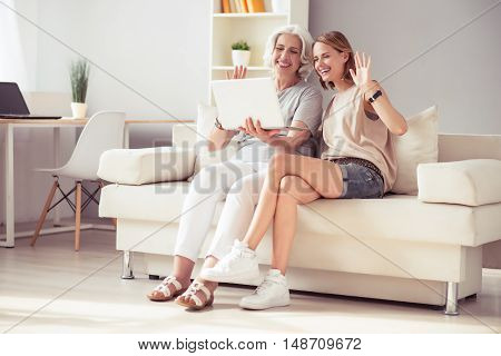 Make a pause. Cheerful delighted woman and her aged mother sitting on the couch and using laptop while talking through the Internet