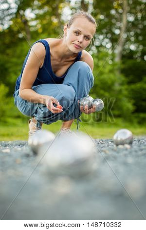 Young woman playing Boules (Petanque) game