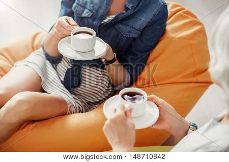 Refresh your mind. Top view of pleasant women sitting in the puffs and drinking coffee while resting