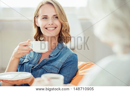 In a good mood. Joyful beautiful content woman sitting in the puff and drinking tea while talking with her senior mother