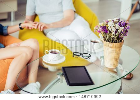 Warm atmosphere. Close up of coffee table standing in the room while pleasant mother and adult daughter sitting in the background
