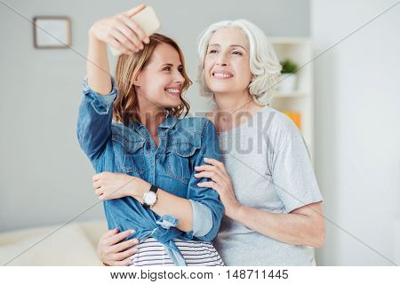 Share true emotions. Positive content smiling woman and her aged mother making selfies and expressing joy while resting at home