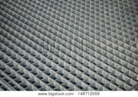 The gray metal grill on the floor. Abstraction.