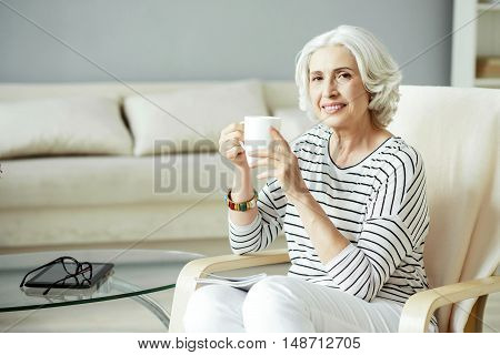 Enjoy every day. Positive content woman smiling and drinking tea while resting at home