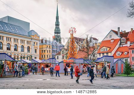 People Walking Around Christmas Market At Livu Square In Riga