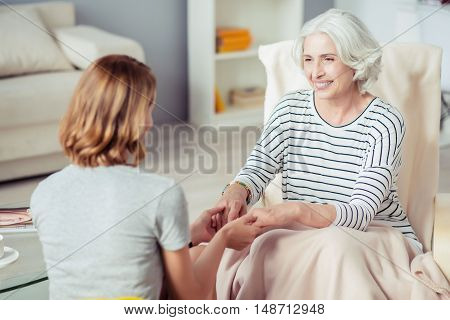 No gap between generations. Loving aged smiling woman sitting in the armchair and expressing joy while holding hands of her adult daughter