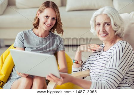 Spend time together. Cheerful smiling aged woman resting with her granddaughter and using laptop while sitting at home