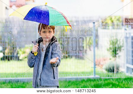 Seven Years Old Boy Standing At The Rain