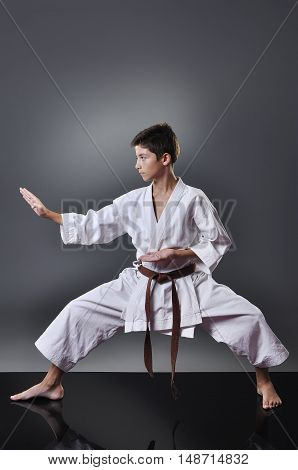 Handsome Young Male Karate Doing Kata On The Gray Background