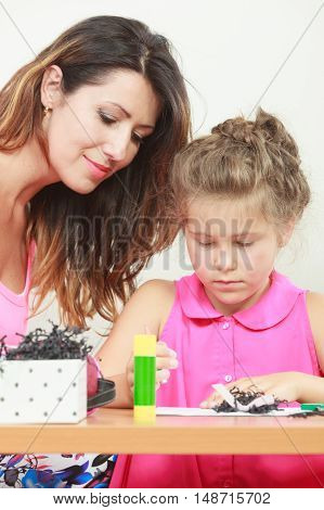 Mom helping daughter with homework. Parenting cooperation common fun