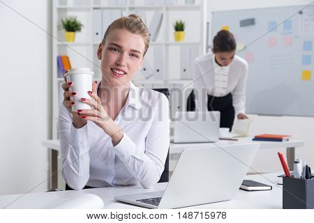 Smiling businesswoman holding white coffee cup looking to camera. Her colleague at background is checking her notes and working hard. Concept of good and bad employees.