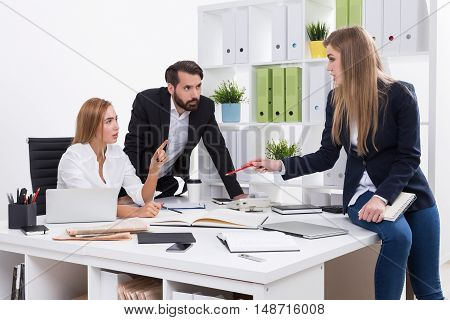 Business meeting in office. Woman boss is giving orders to her subordinates. Businessman looking at colleague. Concept of brainstorming