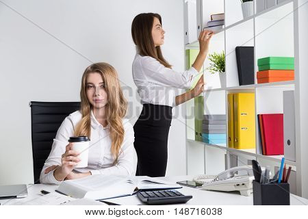 Blond business lady is drinking coffee at her workplace. Her colleague is making order at book shelves.