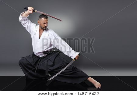 Handsome Young Black Belt Male Karate Posing With Swords On The Gray Background